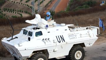 A UN peacekeeper (UNIFIL) patrols the border with Israel in the village of Khiam