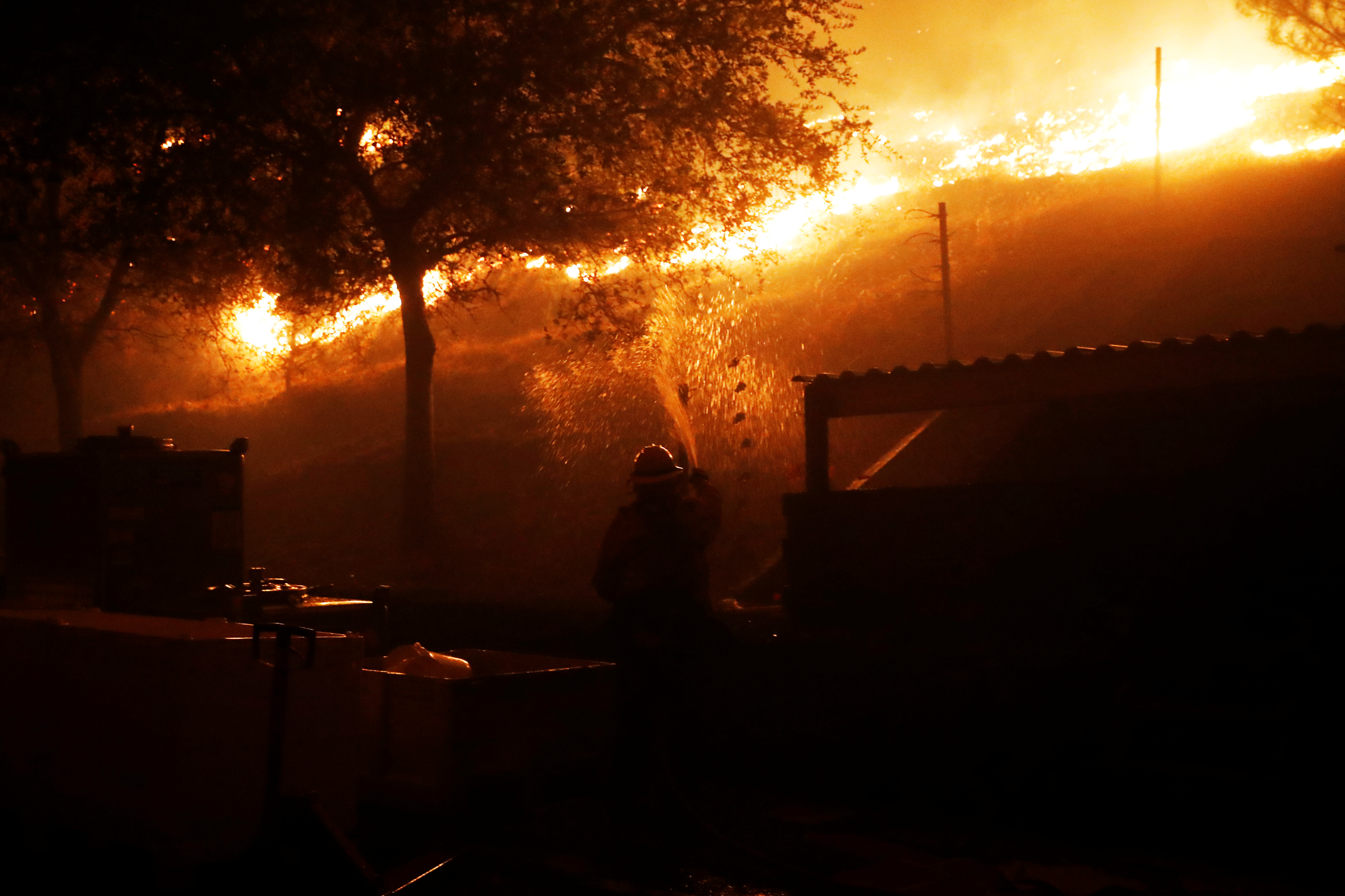 A firefighter defends a structure against approaching flames while in Geyserville.