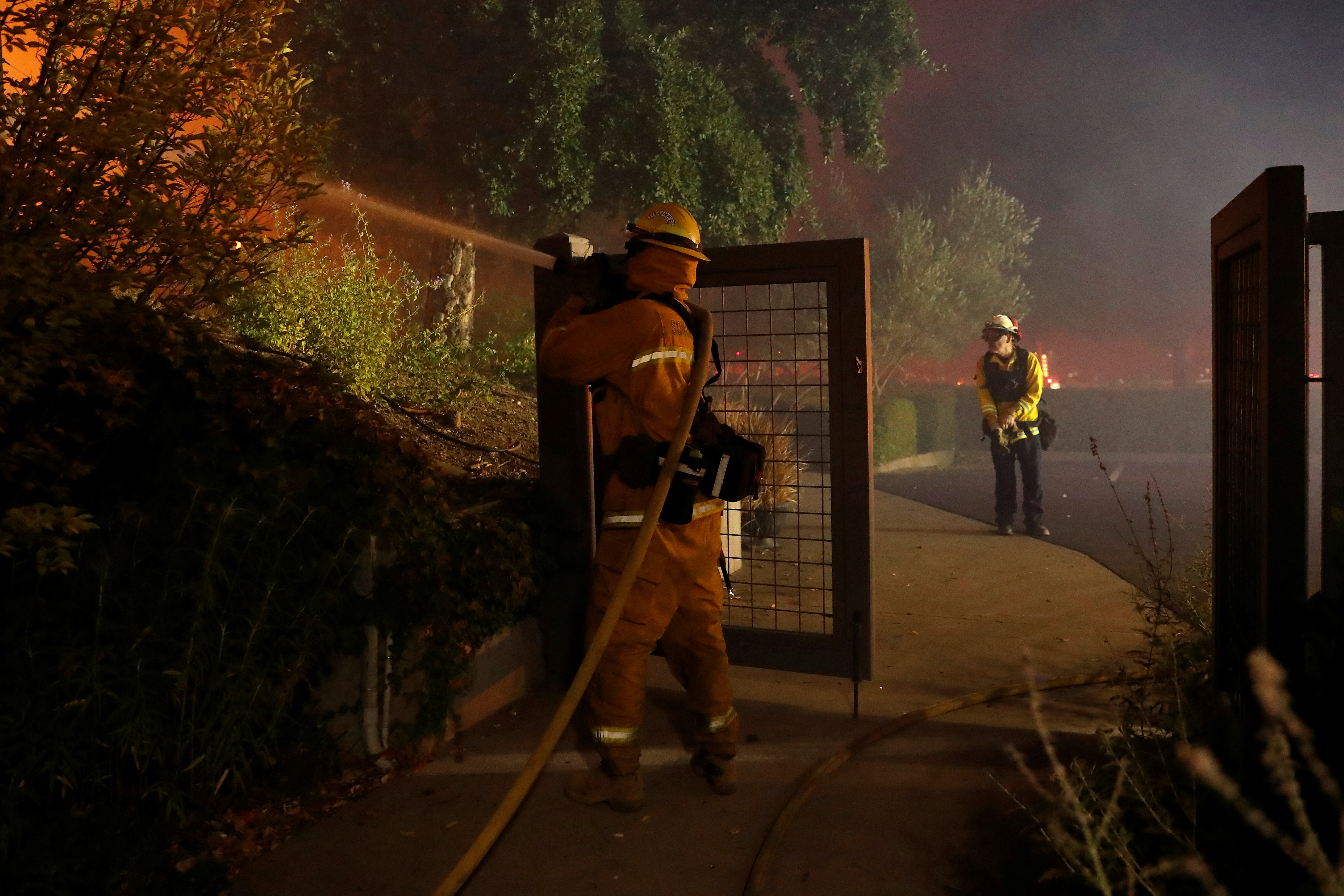 A firefighter hoses a hot spot while battling the Kincade fire at in Geyserville.