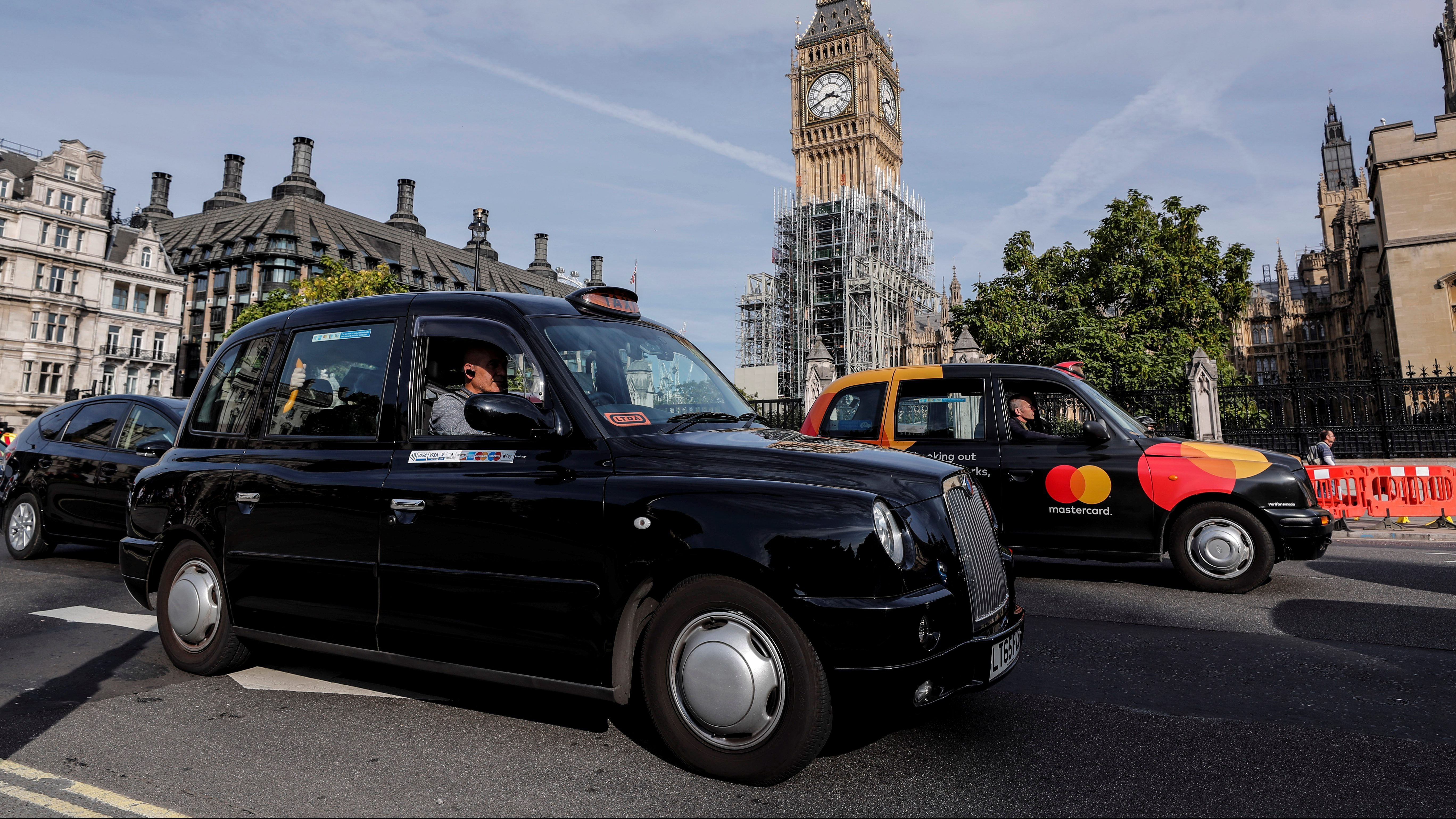 Black taxis pass the Houses of Parliament in London