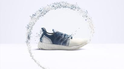 An image shows bits of plastic flowing in a circle around the Futurecraft.Loop sneaker