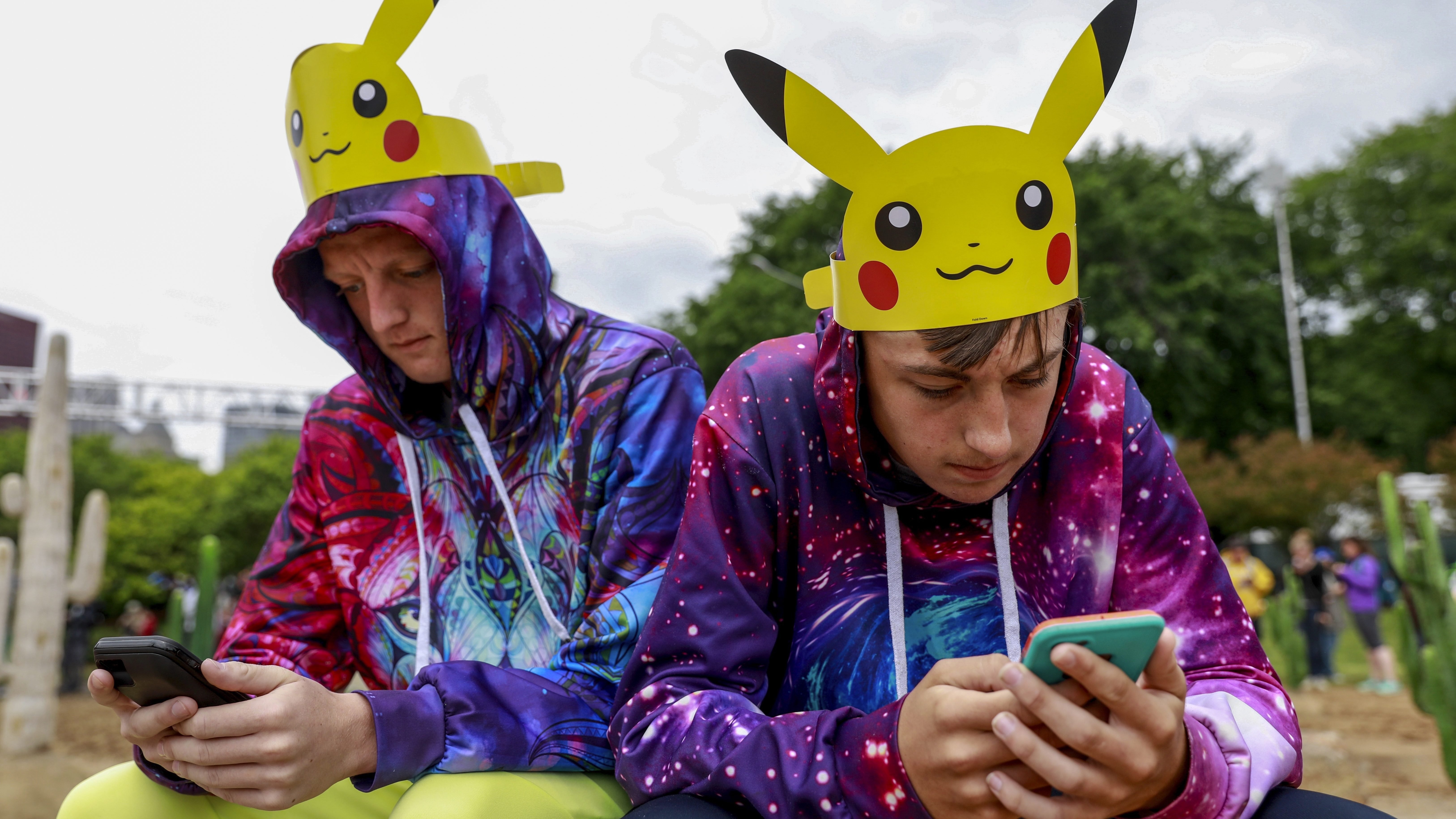 Two brothers in hoodies and Pikachu hats play Pokemon Go on their phones