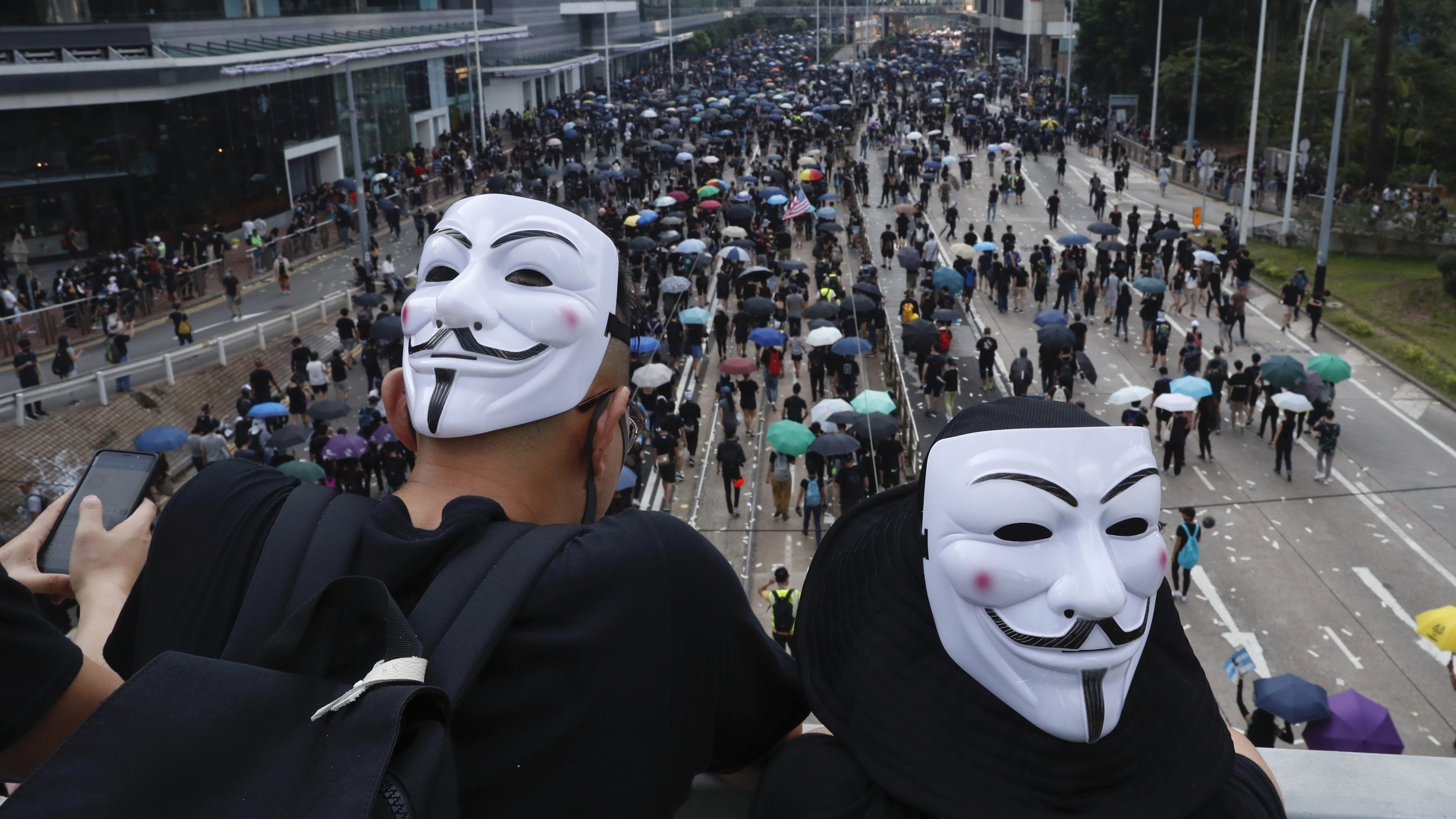 """Anti-government protesters wearing masks march past police headquarters in Hong Kong, Tuesday, Oct. 1, 2019. Thousands of black-clad pro-democracy protesters defied a police ban and marched in central Hong Kong on Tuesday, urging China's Communist Party to """"return power to the people"""" as the party celebrated its 70th year of rule."""