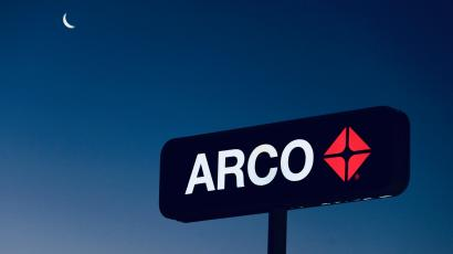 Arco gas station sign against the sky and a sliver of oon.