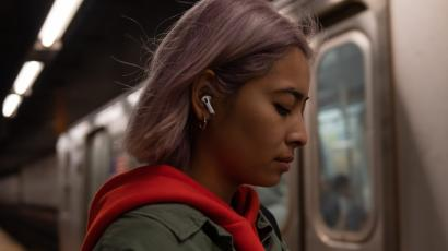 A woman wearing AirPods Pro on the subway