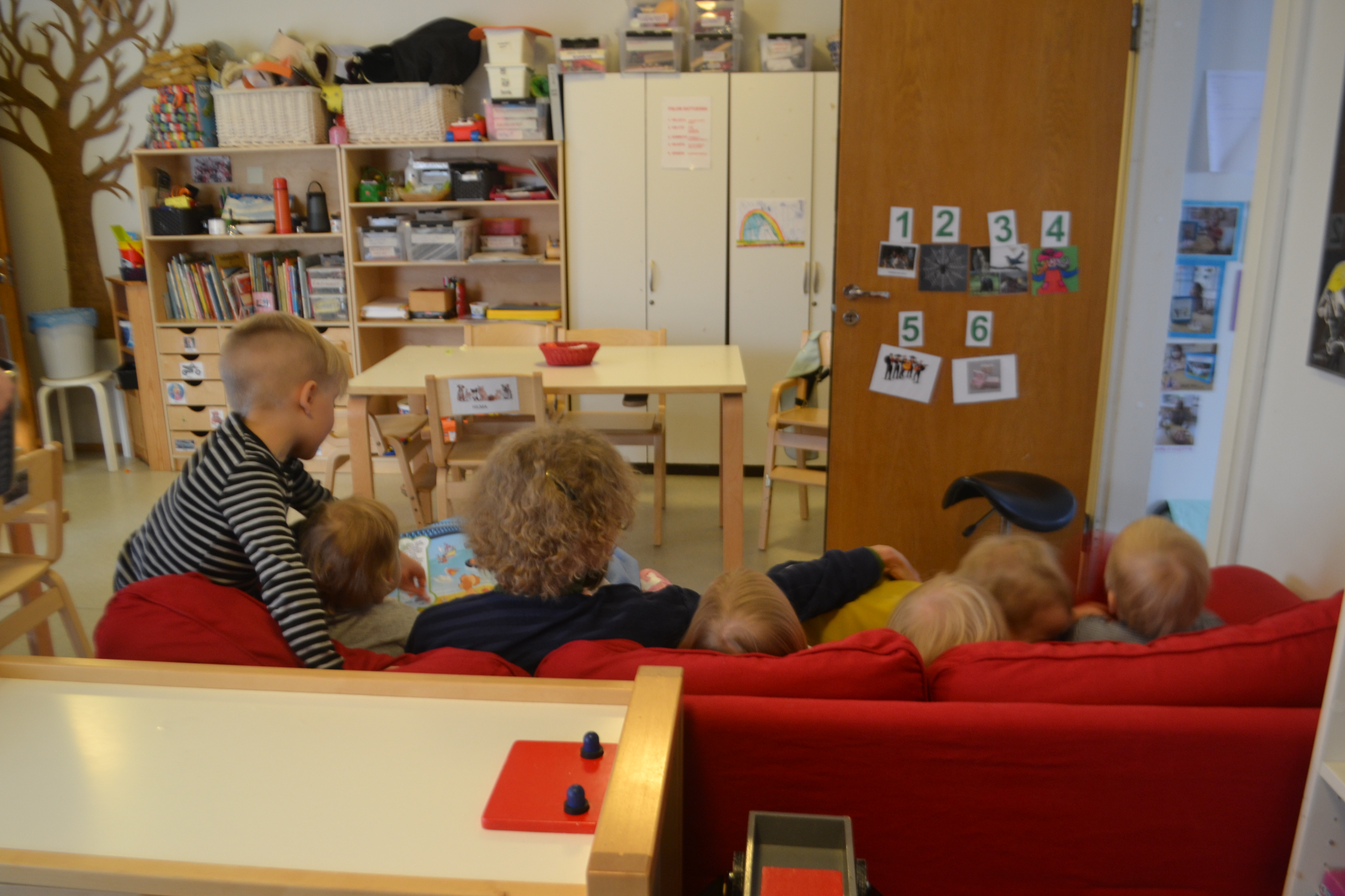 A view of Marjatta on the couch reading to a group of children from the back