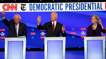 Democratic presidential candidate Sen. Bernie Sanders, I-Vt., left, former Vice President Joe Biden, center, and Sen. Elizabeth Warren, D-Mass., raise their hands to speak.