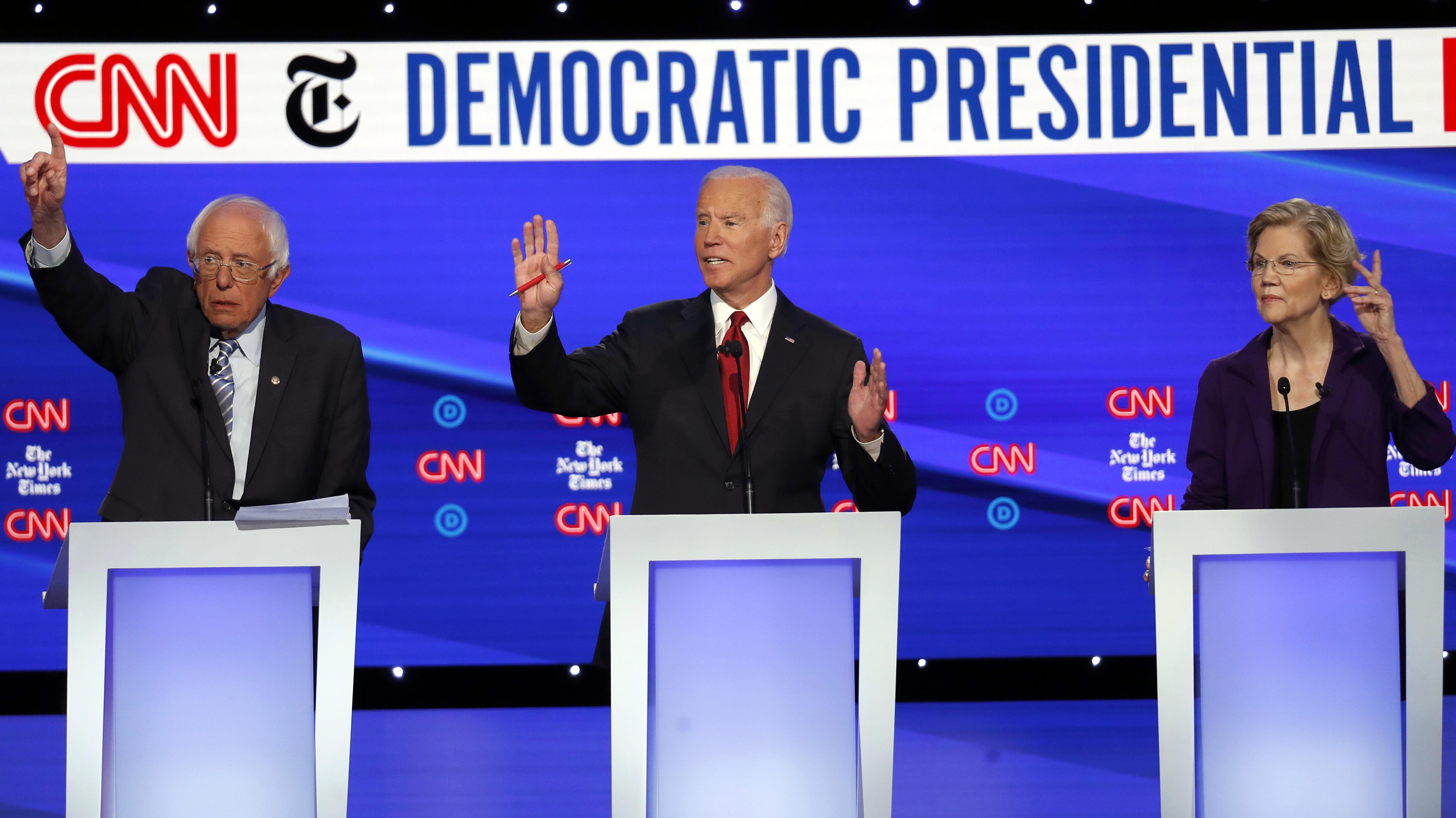 Democratic presidential candidate Sen. Bernie Sanders, I-Vt., left, former Vice President Joe Biden, center, and Sen. Elizabeth Warren, D-Mass., raise their hands to speak.