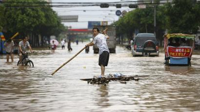 Resident paddling a homemade raft on a flooded street