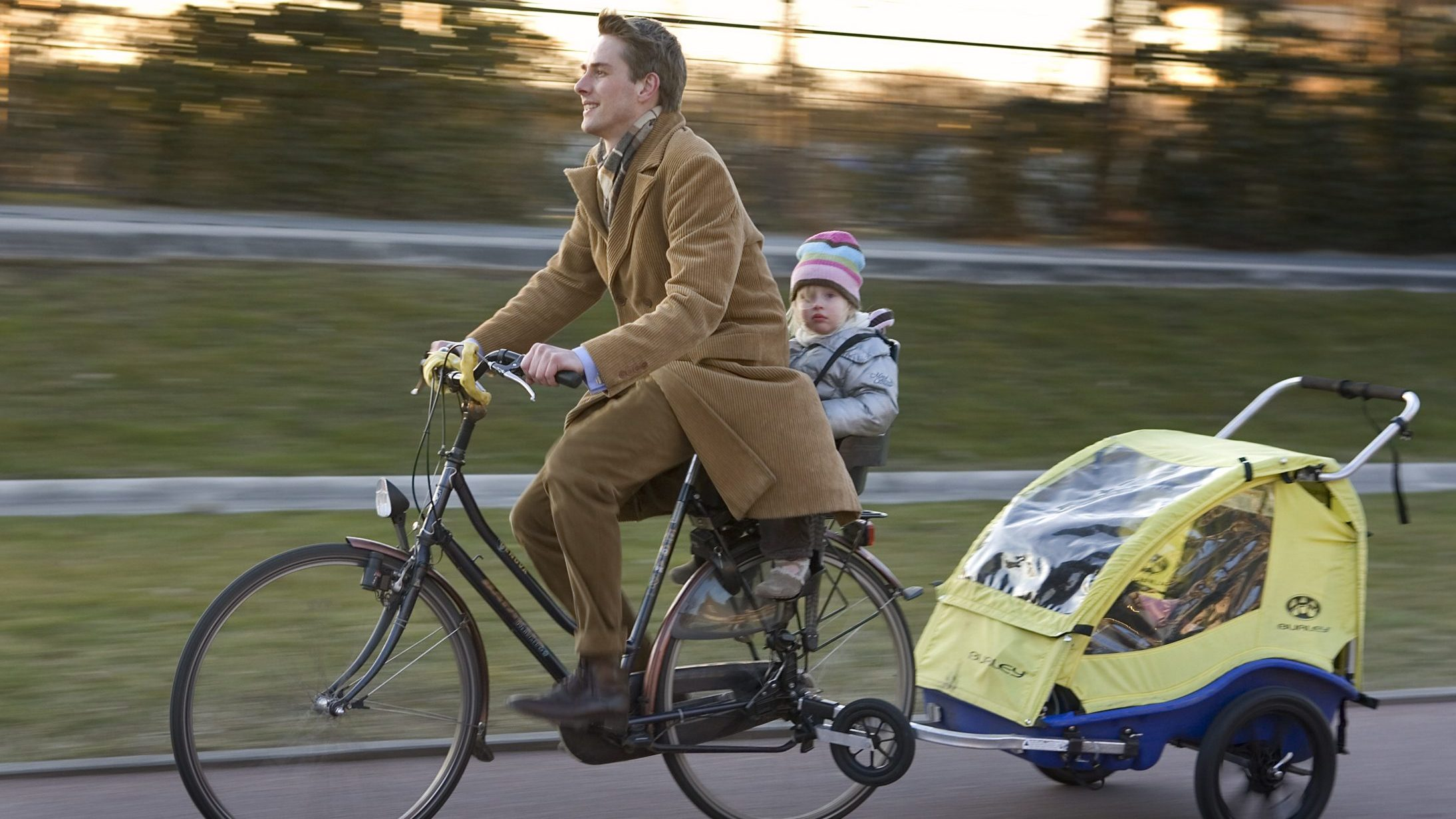 A man rides his bicycle with a baby and a trolley behind him