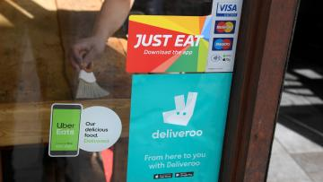 Signage for Just Eat is seen next to Uber Eats and Deliveroo advertisements on the window of a restaurant in London, Britain, August 5, 2019.