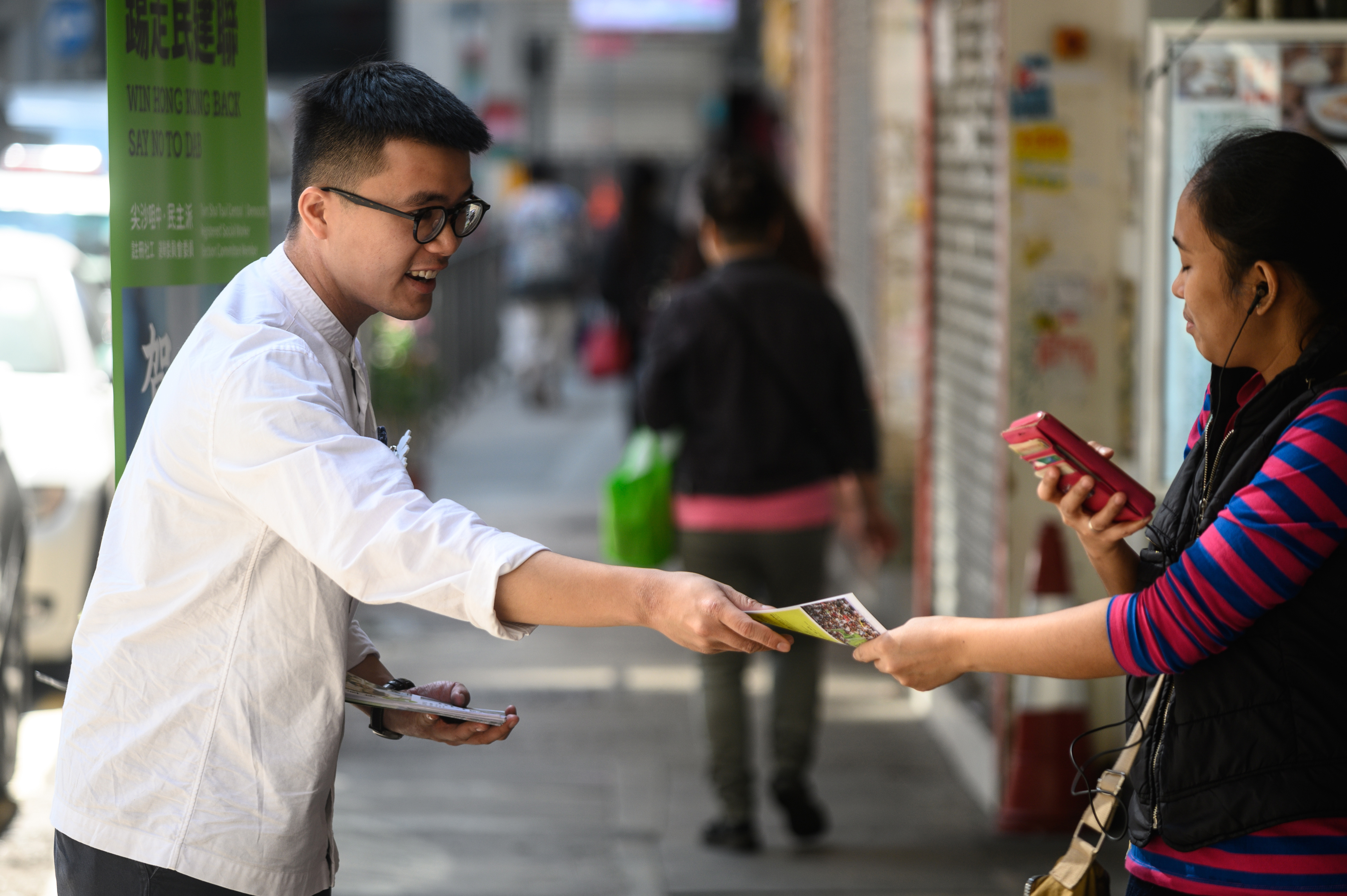 In this picture taken on Nov. 21, 2019, district council election candidate Isaac Ho hands out leaflets to people in Tsim Sha Tsui in Hong Kong.