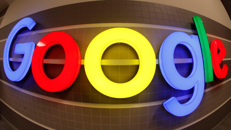 An illuminated Google logo is seen inside an office building in Zurich
