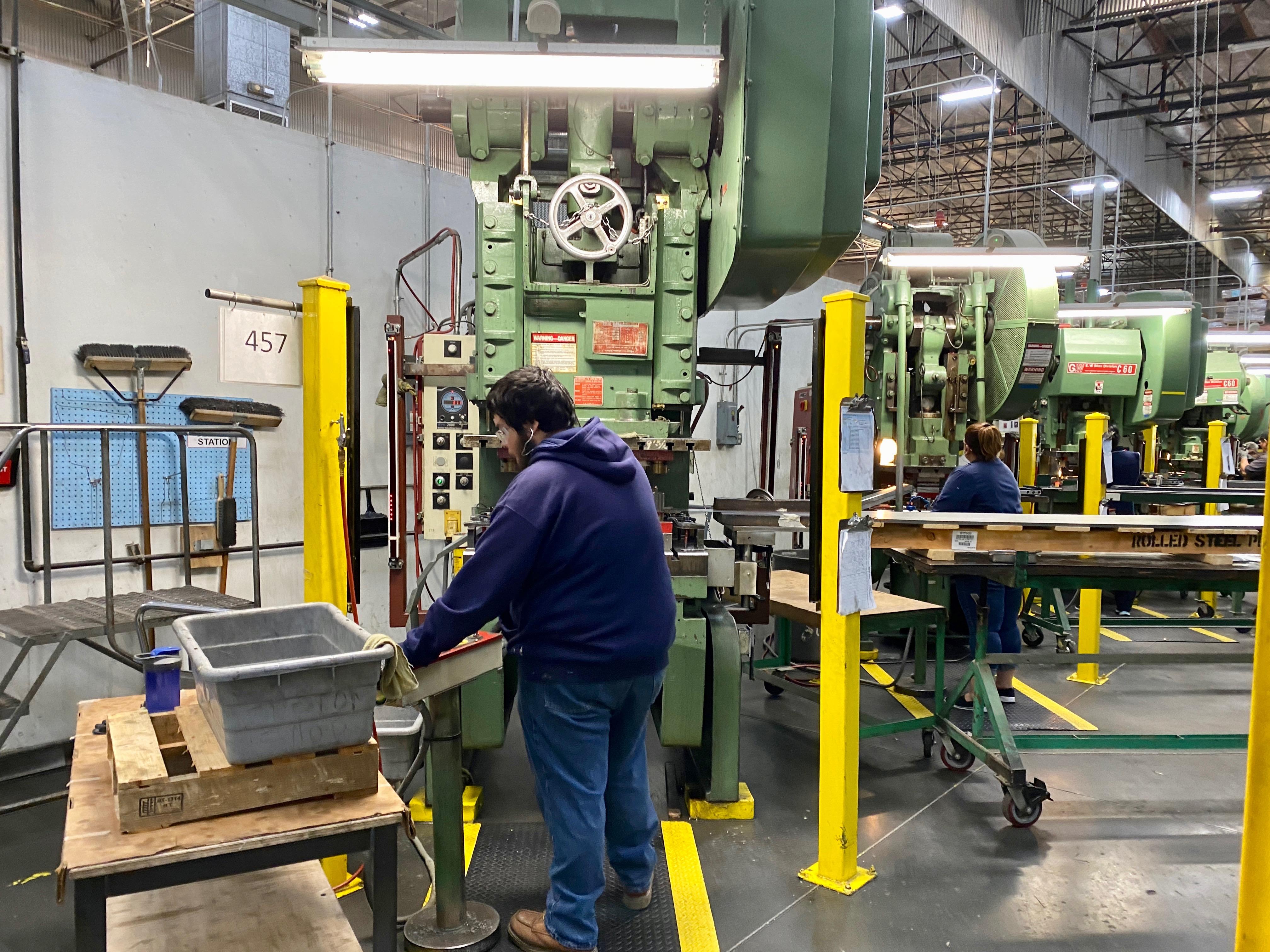 Fender maquinistas operando máquinas em sua fábrica Corona