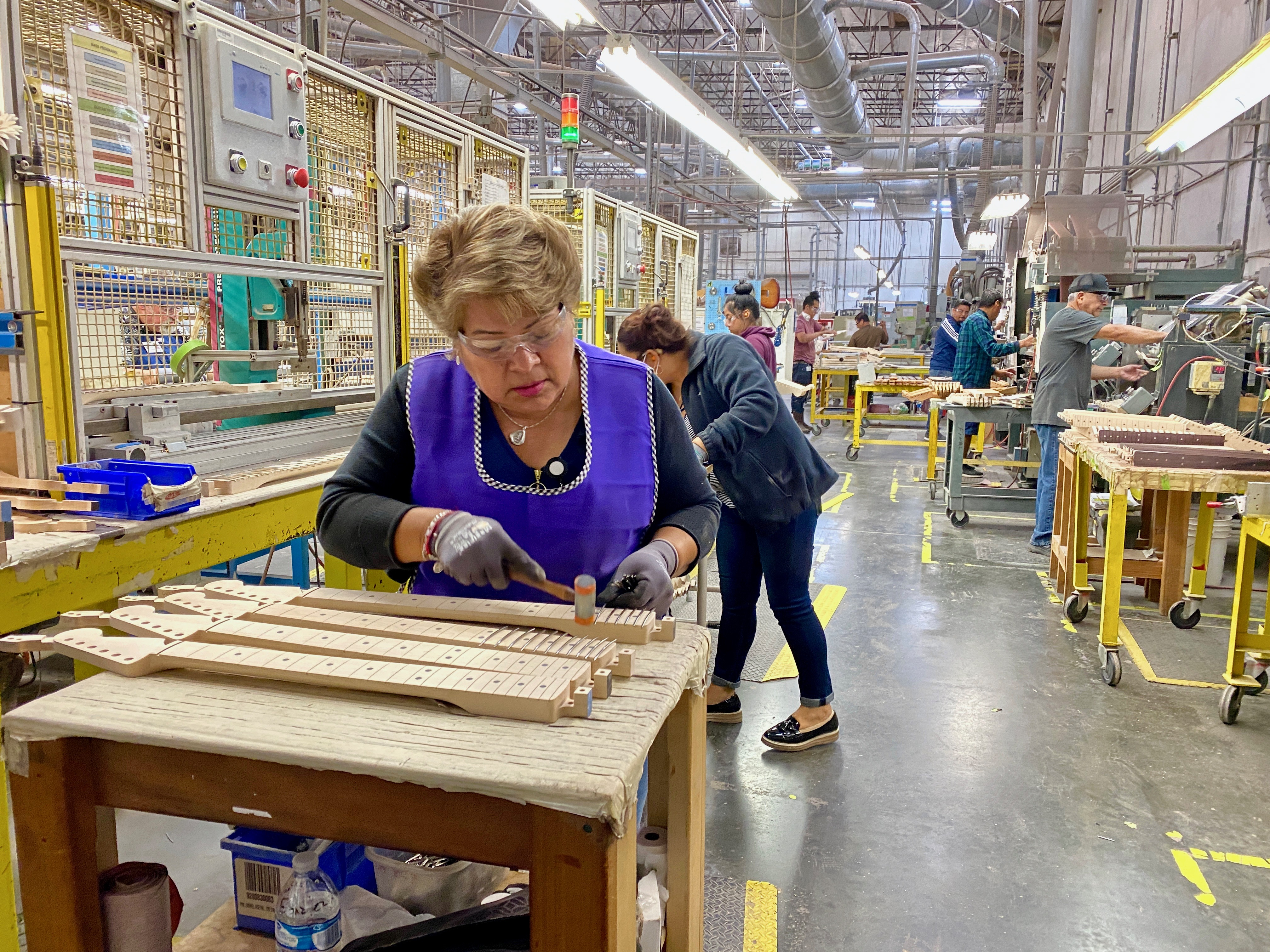 A worker hammering frets into a neck at the plant
