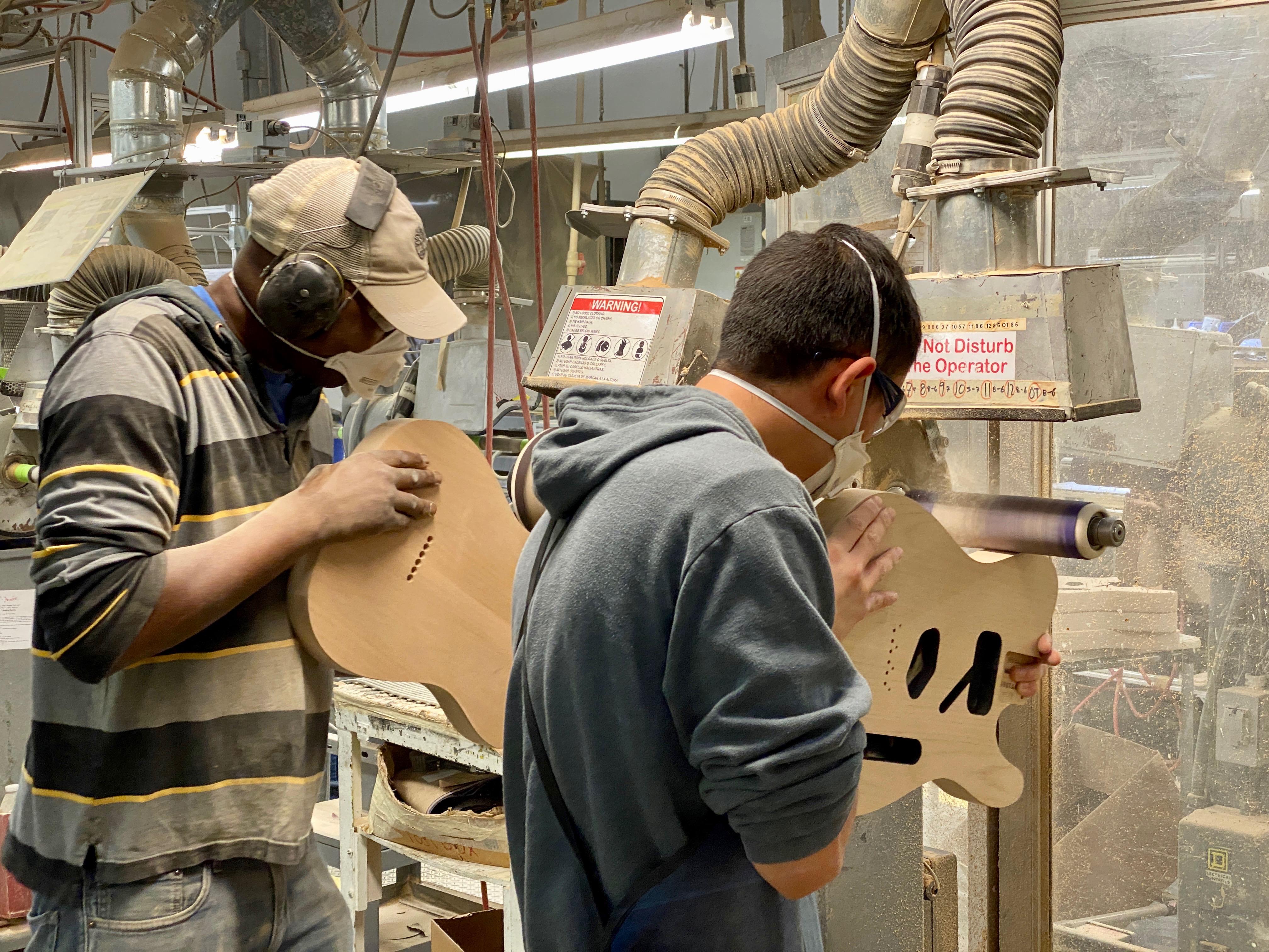 Trabalhadores lixando corpos de violão na fábrica da Fender.