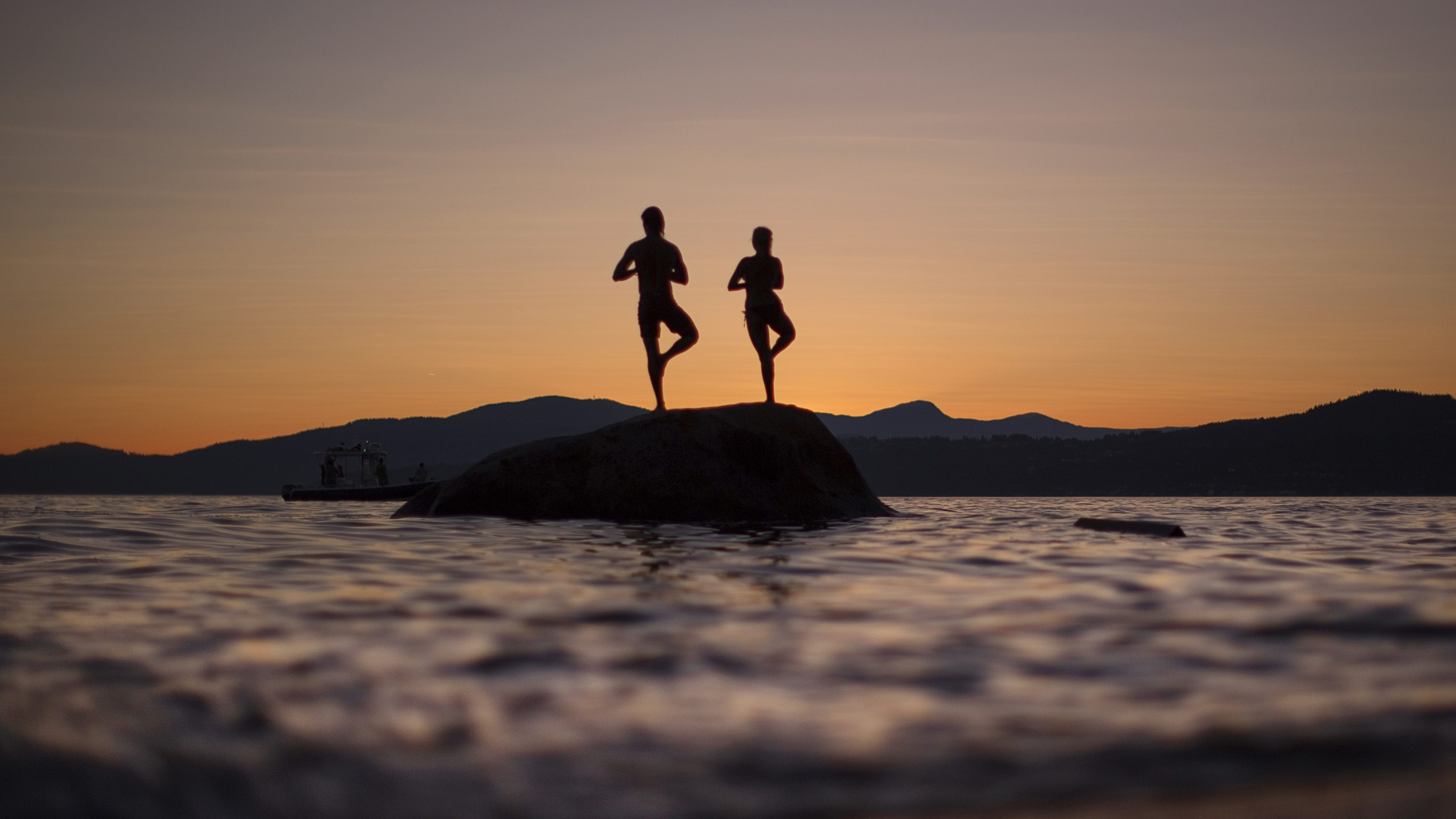 Two people stand on a rock facing the sunse