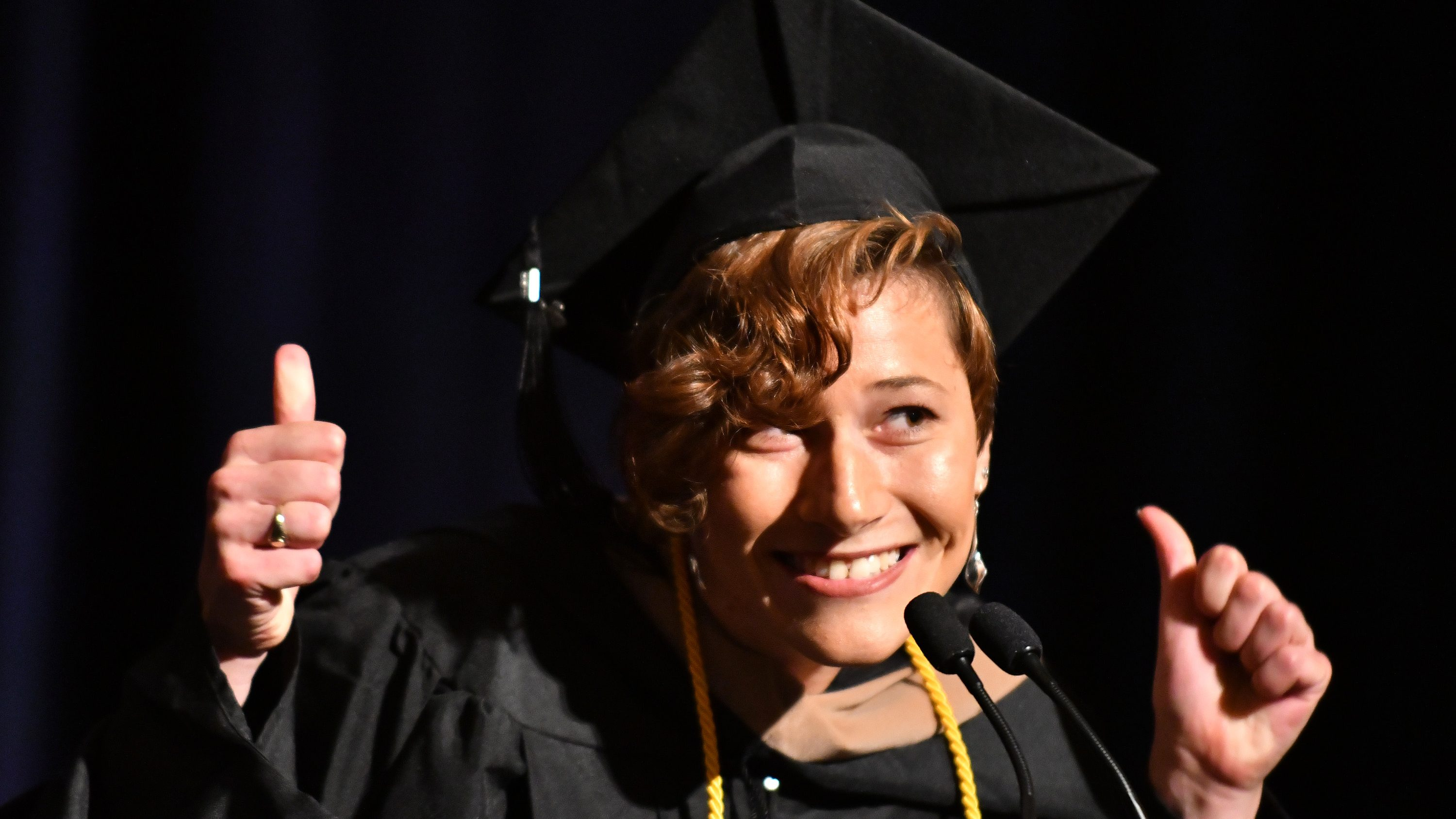 a woman in graduation robe and hat gives the thumbs up