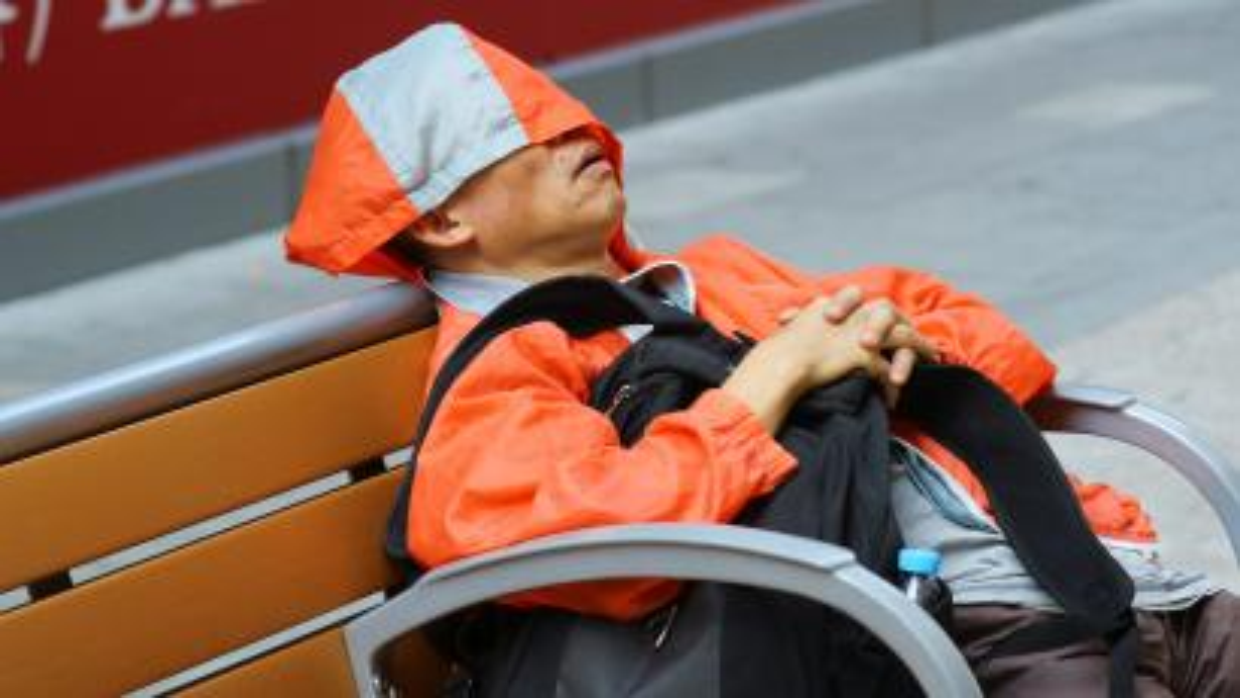 Man in orange jacket asleep on a bench.