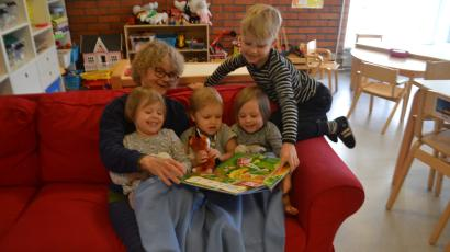 Communal grandmother Marjatta Ahonen reads a book to children on a red couch.