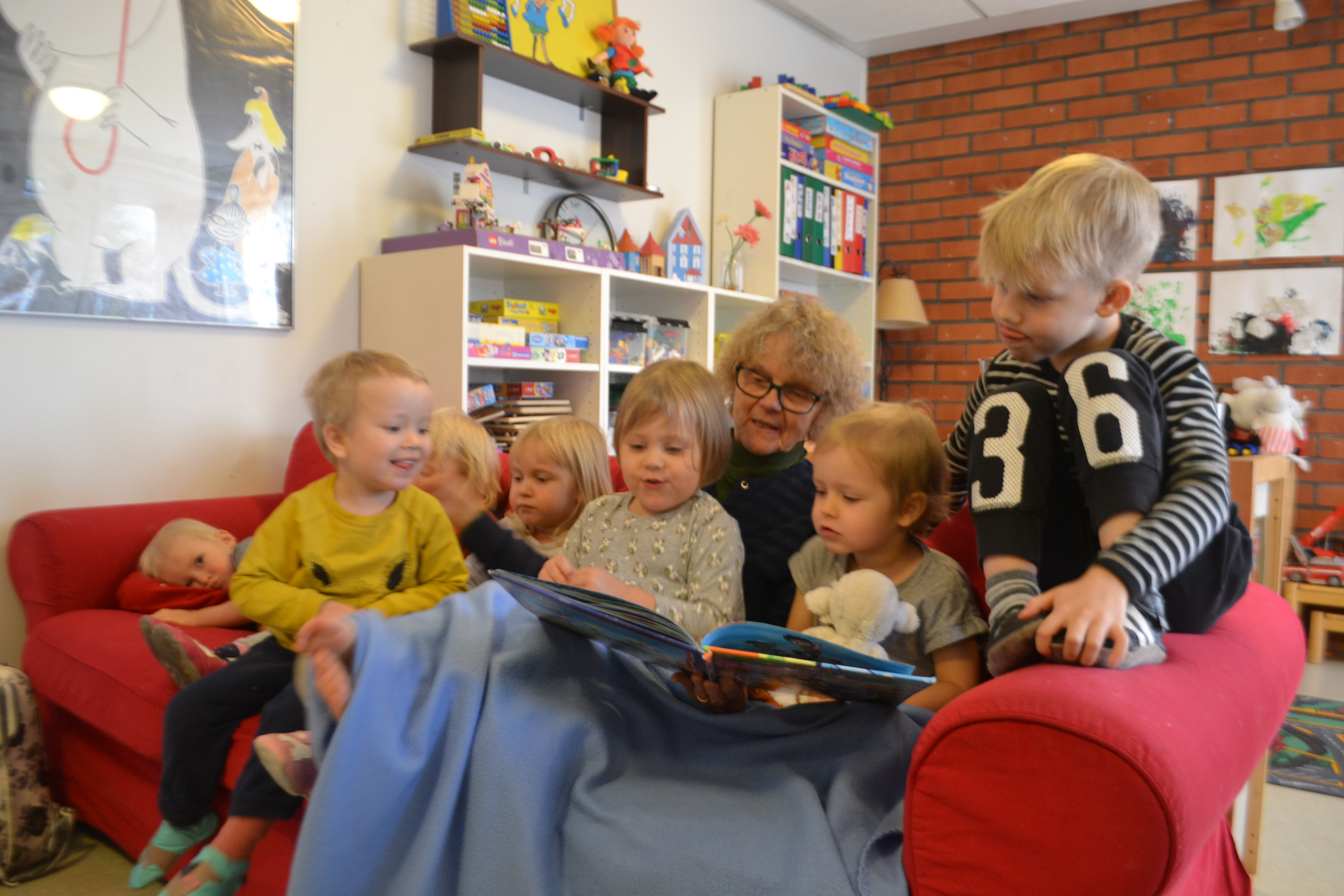 A group of children sit on the couch with Marjatta as she reads them a book
