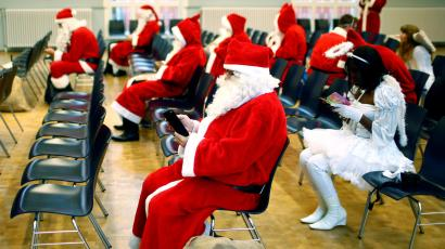People dressed in Santa Claus and Christmas angels costumes use their smartphones.