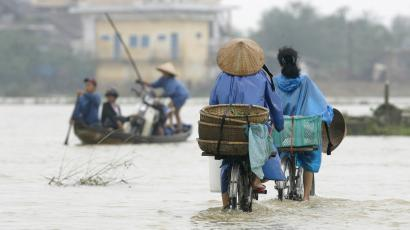 Residents ride their bicycles on a flooded road in Vietnam's central Thua Thien Hue province