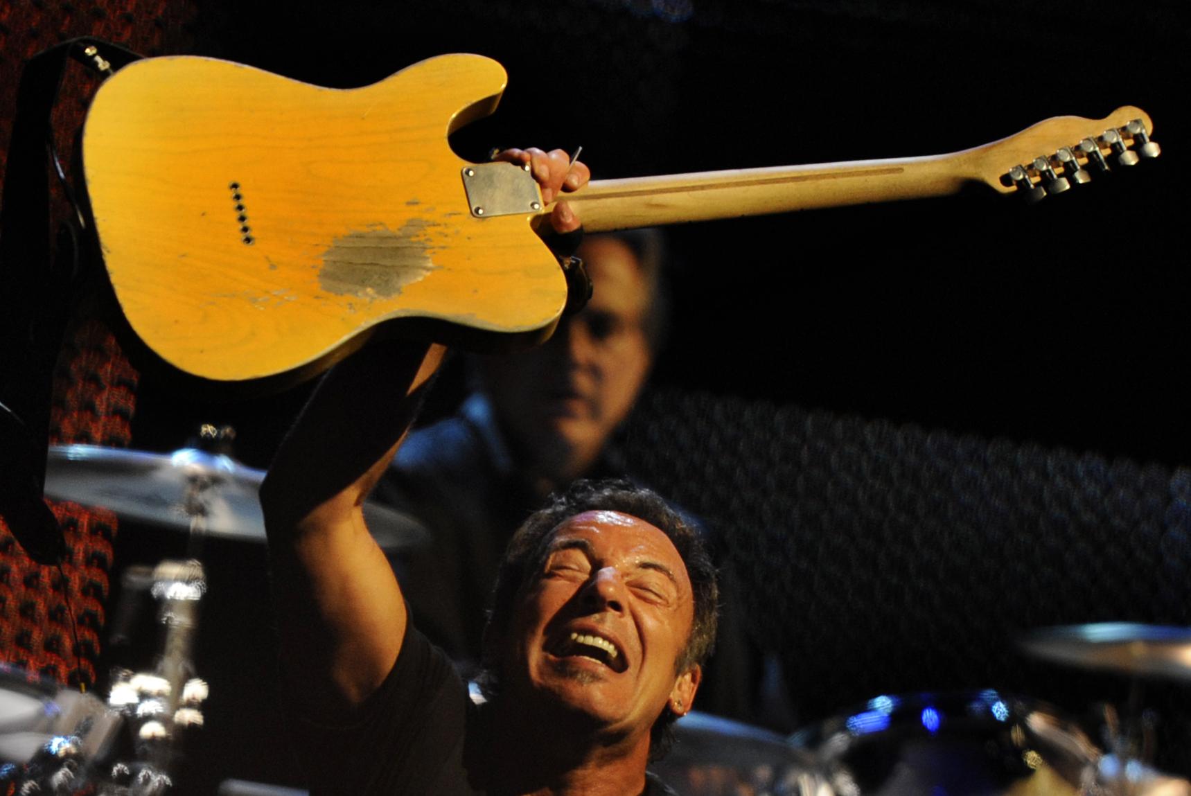 Bruce Springsteen holding up a Fender guitar