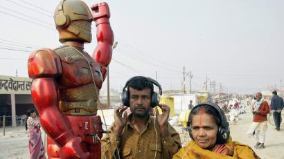 Hindu devotees wearing headsets listen to a fortune-telling machine at Sangam in Allahabad