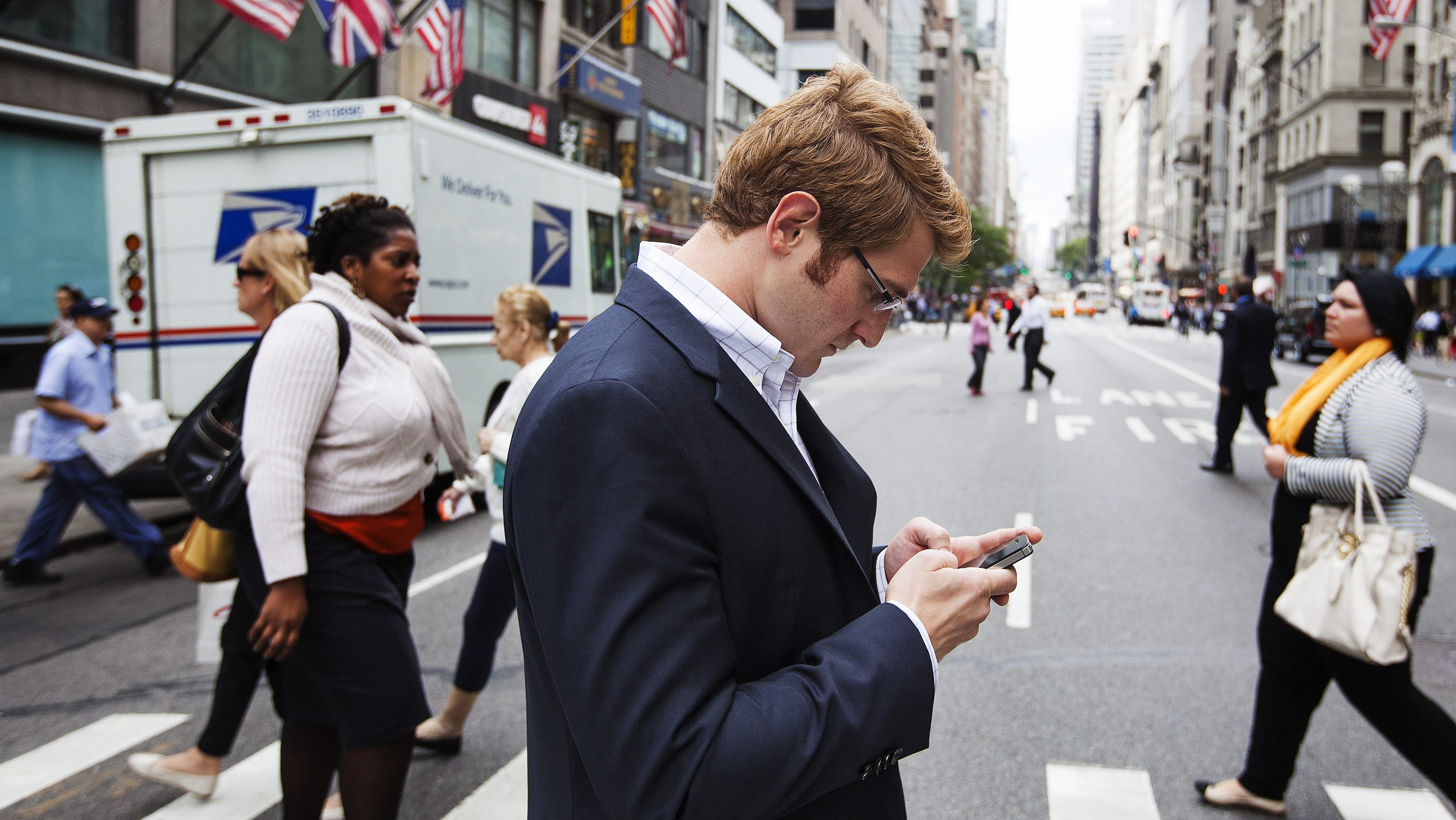 A man uses his Apple iPhone while walking across 5th Avenue in New York