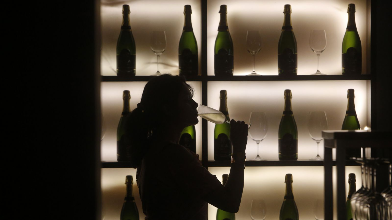 A woman poses with a glass of wine at a tapas bar in Mumbai March 9, 2013. Women who drink, long portrayed as less than respectable by Bollywood movies and still wary of entering most watering holes, are becoming big business in socially conservative India. Picture taken March 9, 2013.