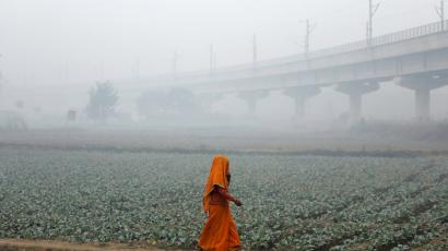 A woman walks across a field on a smoggy morning in New Delhi