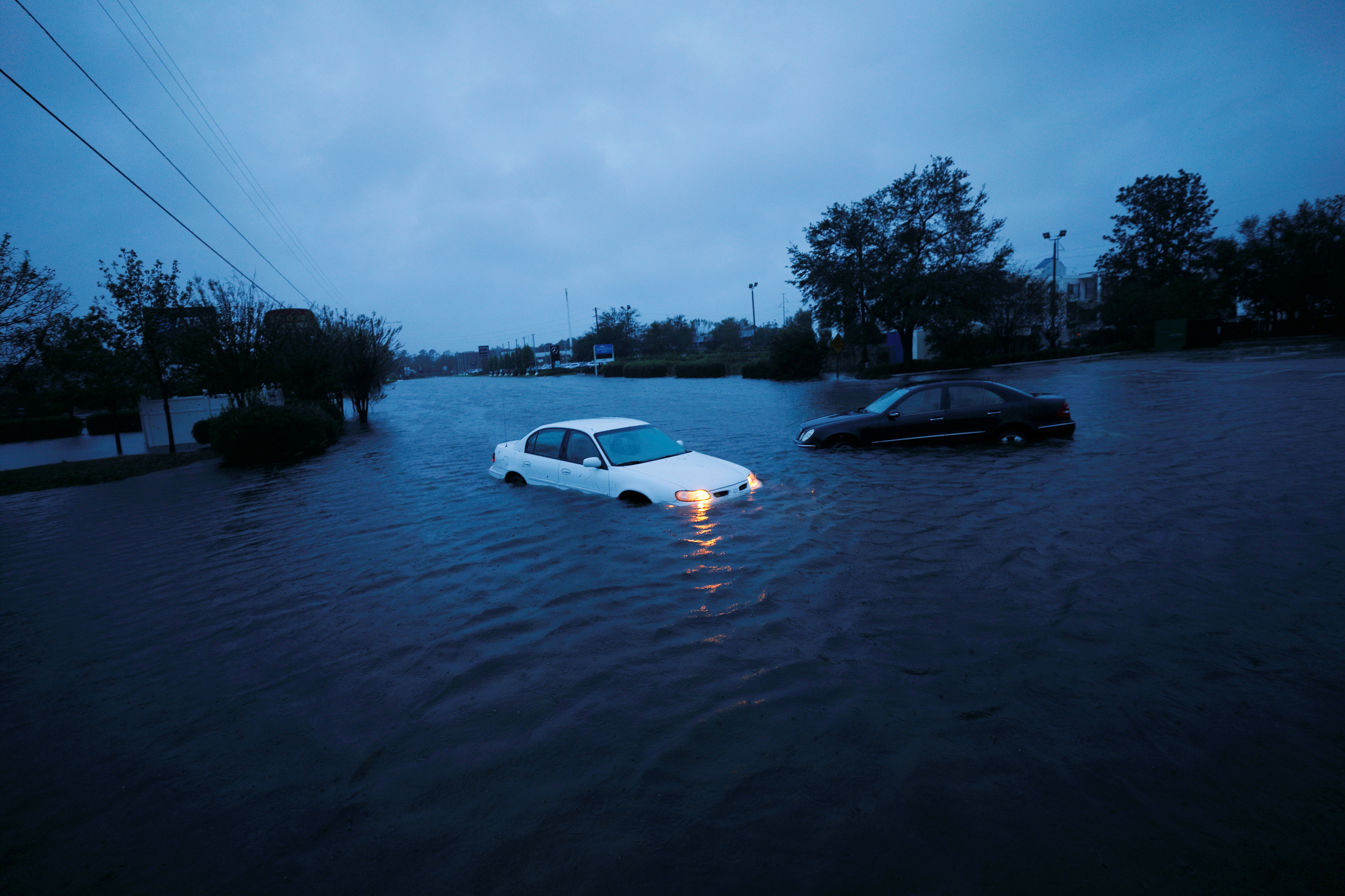 An abandoned car sits flooded on a submerged road at dusk.