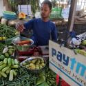 A vendor weighs vegetable next to an advertisement of Paytm, a digital payments firm, hanging amidst his vegetables at a roadside market in Mumbai