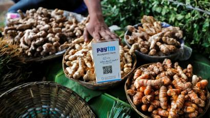 An advertisement board displaying a QR code for Paytm, a digital wallet company, is seen placed amidst vegetables at a roadside vendor's stall in Mumbai