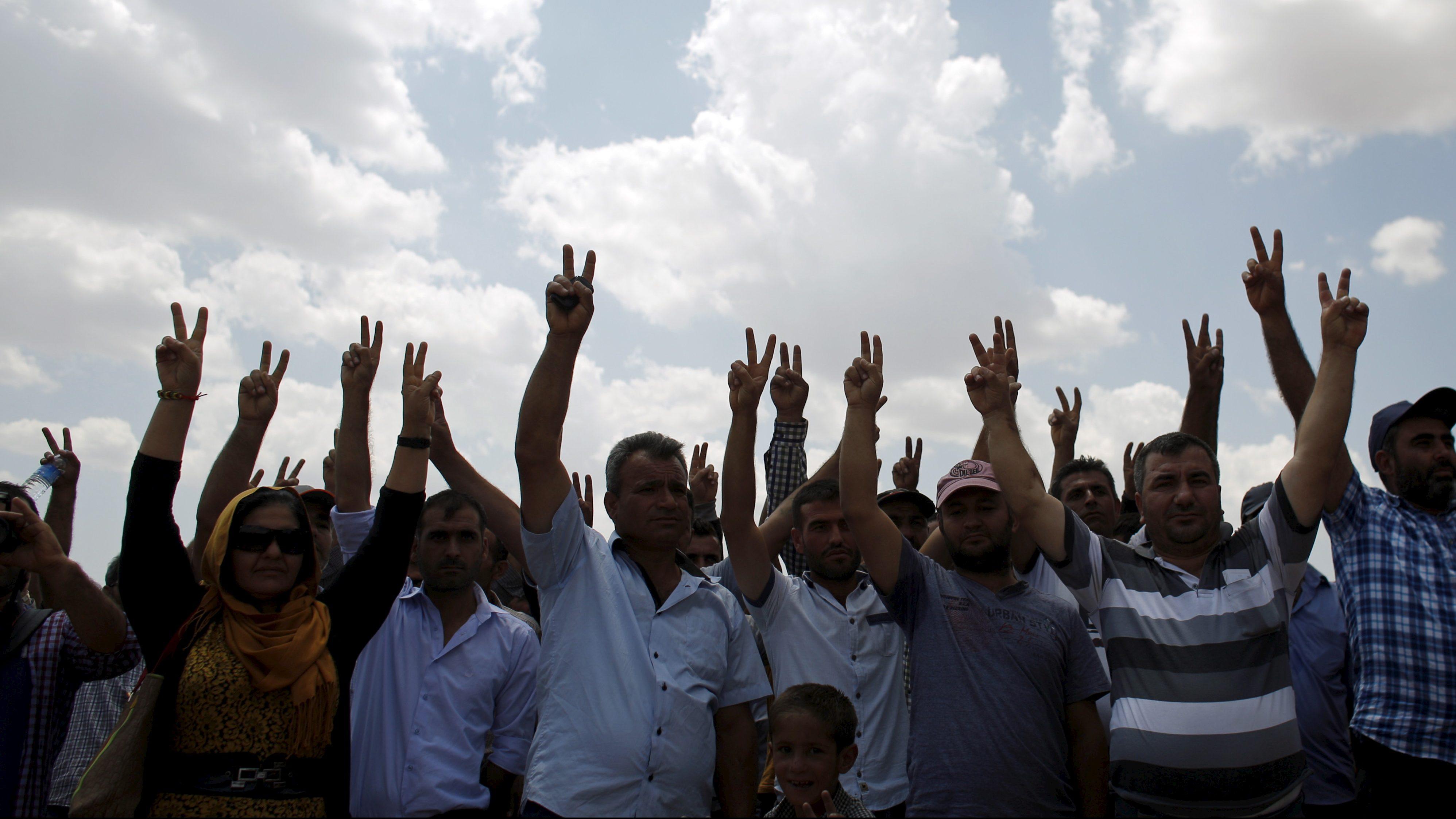 Turkish Kurds flash V-signs as they gather near the Mursitpinar border gate in solidarity with Syrian Kurds in Kobani, in Suruc, Sanliurfa province, Turkey