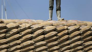 A worker stands on sacks of cement at Sunda Kelapa harbor in Jakarta