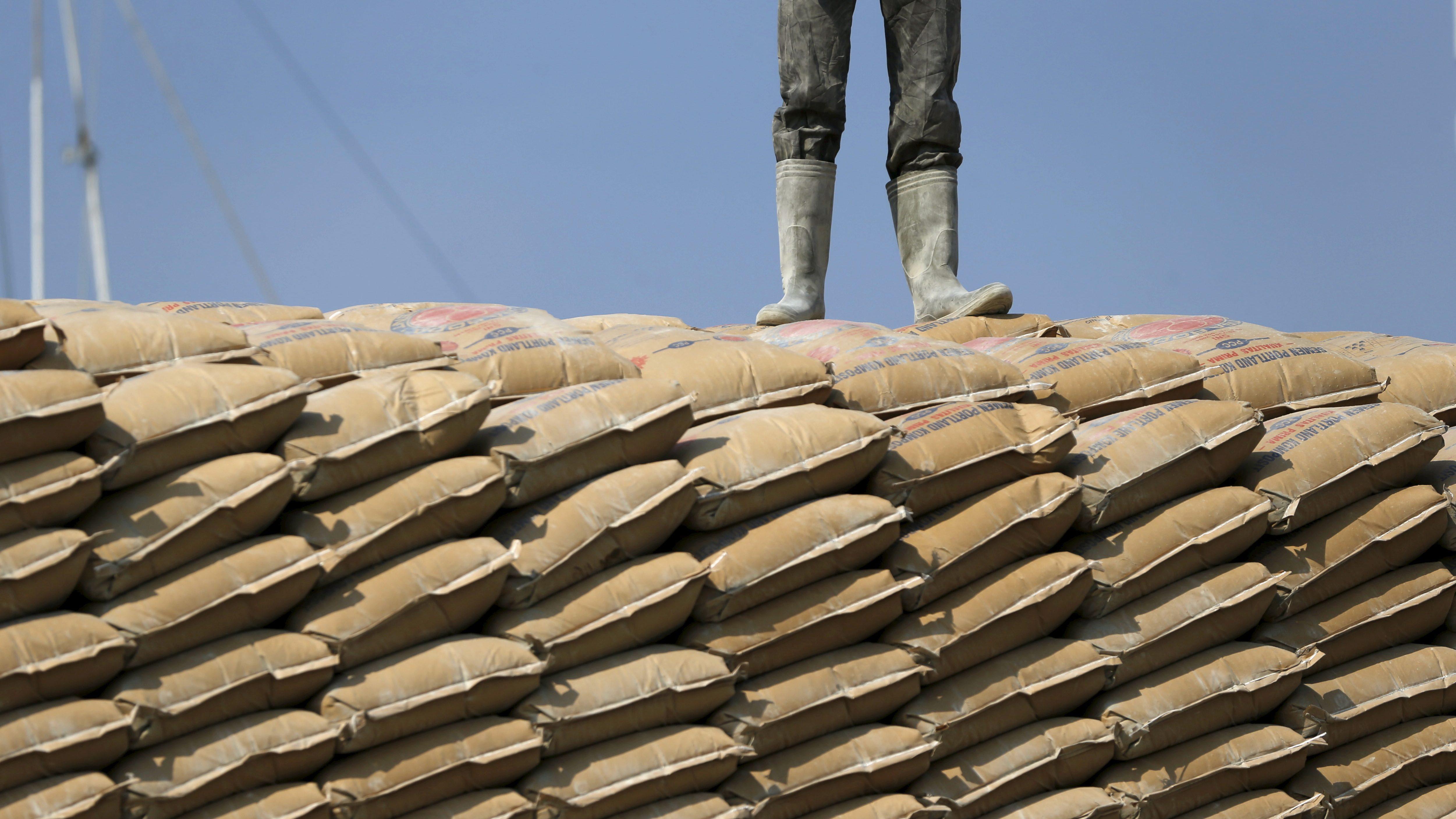 A worker stands on sacks of cement at Sunda Kelapa harbor in Jakarta