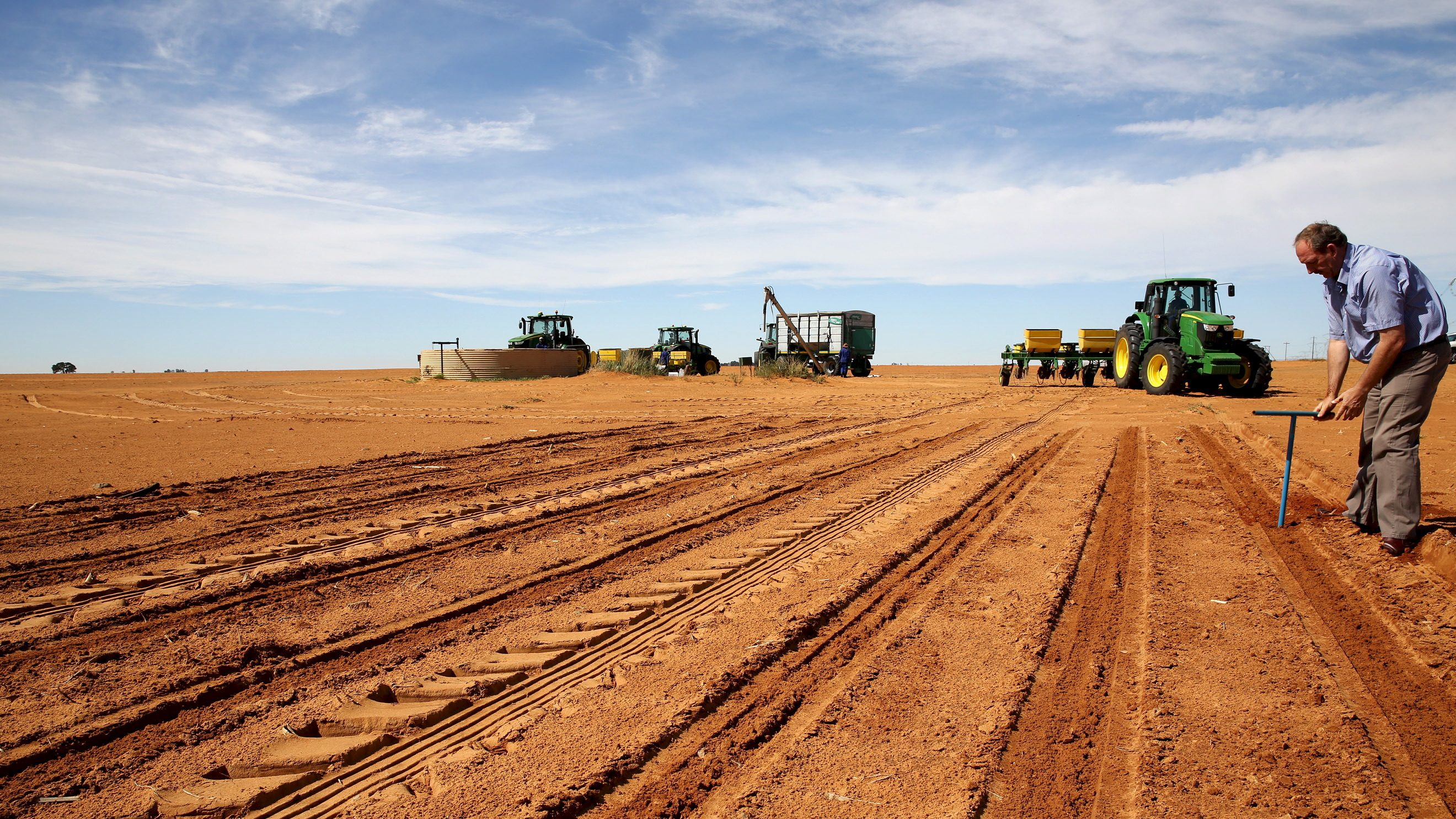 A farmer inspects the soil ahead of planting at a maize field in Wesselsbron, a small maize farming town in the Free State province of South Africa