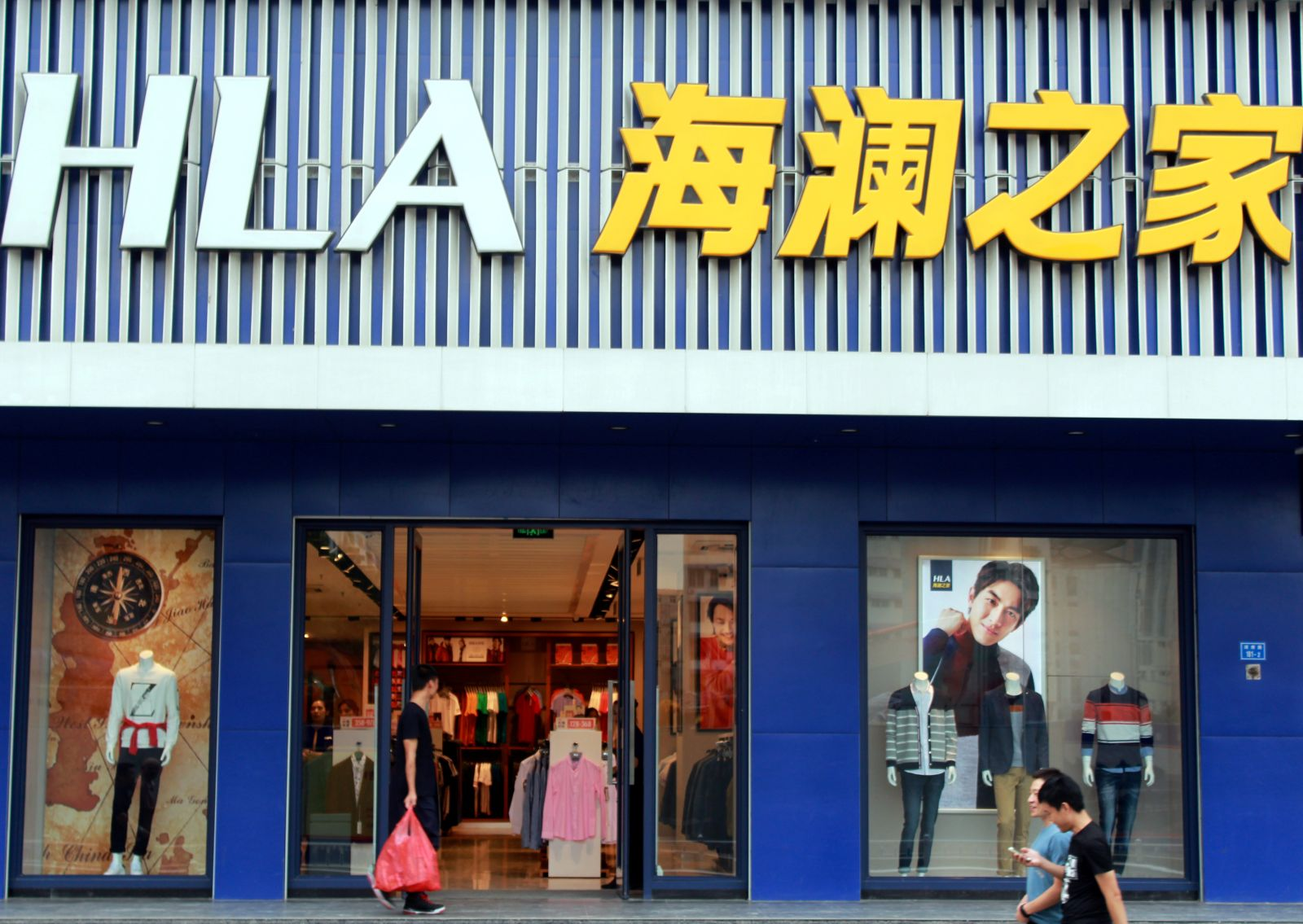 People walk past a store of Chinese menswear brand Heilan Home in Nanjing