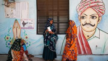 Women wait for a public transport outside a polling station after casting their votes at Sirohi