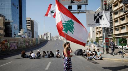 A woman holds a Lebanese flag as she stands at a roadblock during ongoing anti-government protests in Beirut, Lebanon November 4, 2019.