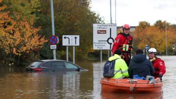 Firefighters and first responders rescue rescue people stranded in a flooded road in central Rotherham, near Sheffield