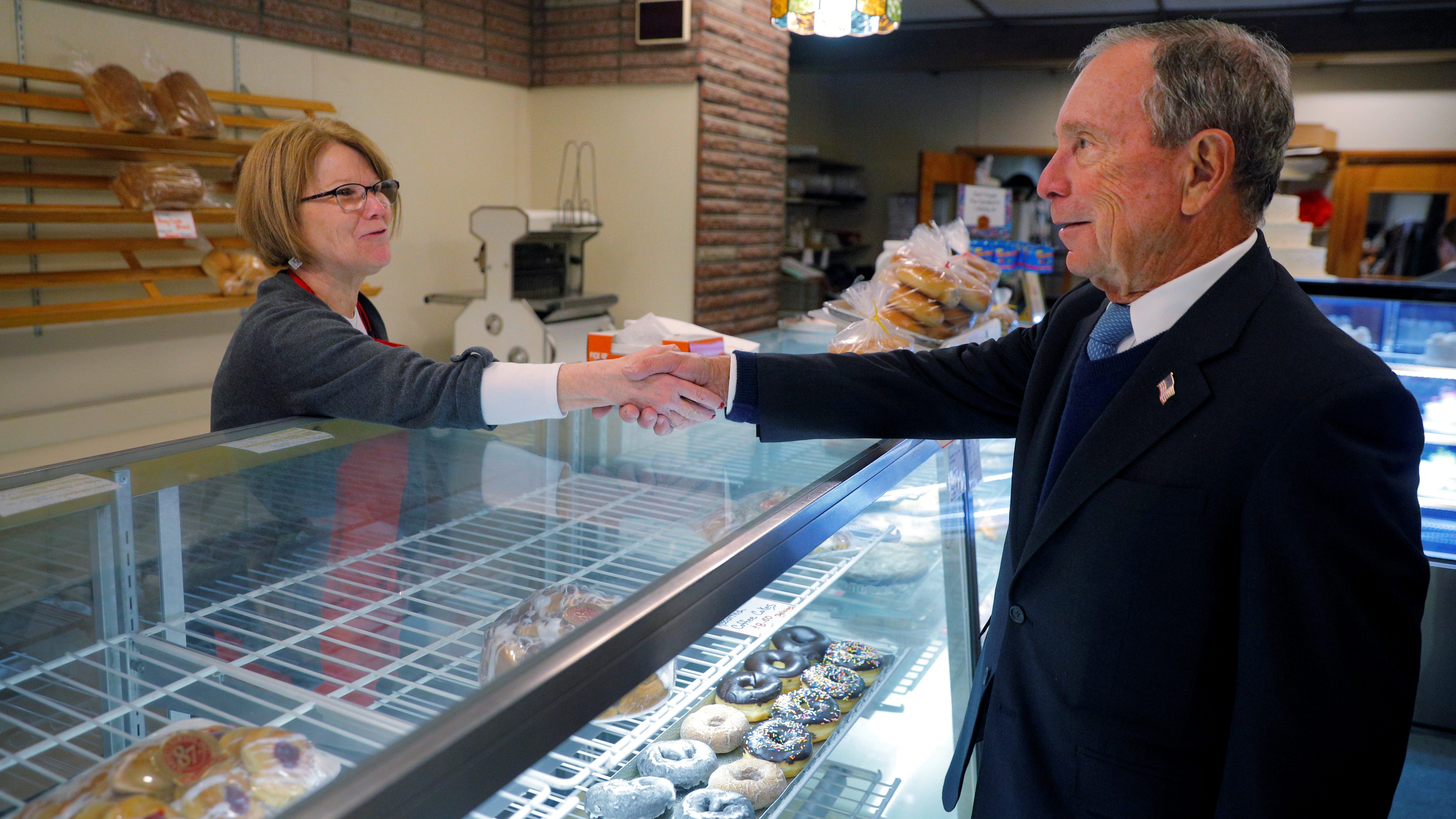 Mike Bloomberg shakes a woman's hand in a bakery in New Hampshire, an early voting state.