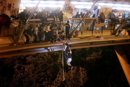 Anti-government protesters trapped inside Hong Kong Polytechnic University abseil onto a highway and escape before being forced to surrender during a police besiege of the campus in Hong Kong, China November 18, 2019. HK01/Handout via REUTERS THIS IMAGE HAS BEEN SUPPLIED BY A THIRD PARTY. HONG KONG OUT. NO COMMERCIAL OR EDITORIAL SALES IN HONG KONG. NO RESALES. NO ARCHIVES TPX IMAGES OF THE DAY - RC2SDD9ROC5A