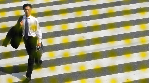 Businessman, seen through a window decorated with dots, crosses a street in Tokyo