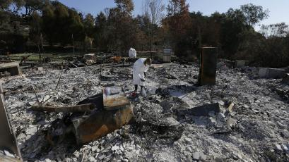 Residents search the remains of homes destroyed by wildfire