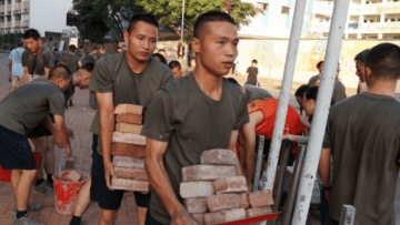 Chinese soldiers clear bricks from barricades near their barracks in Kowloon Tong, November 16, 2019.
