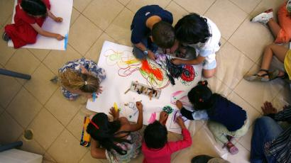 A group of preschoolers draws together on the ground.
