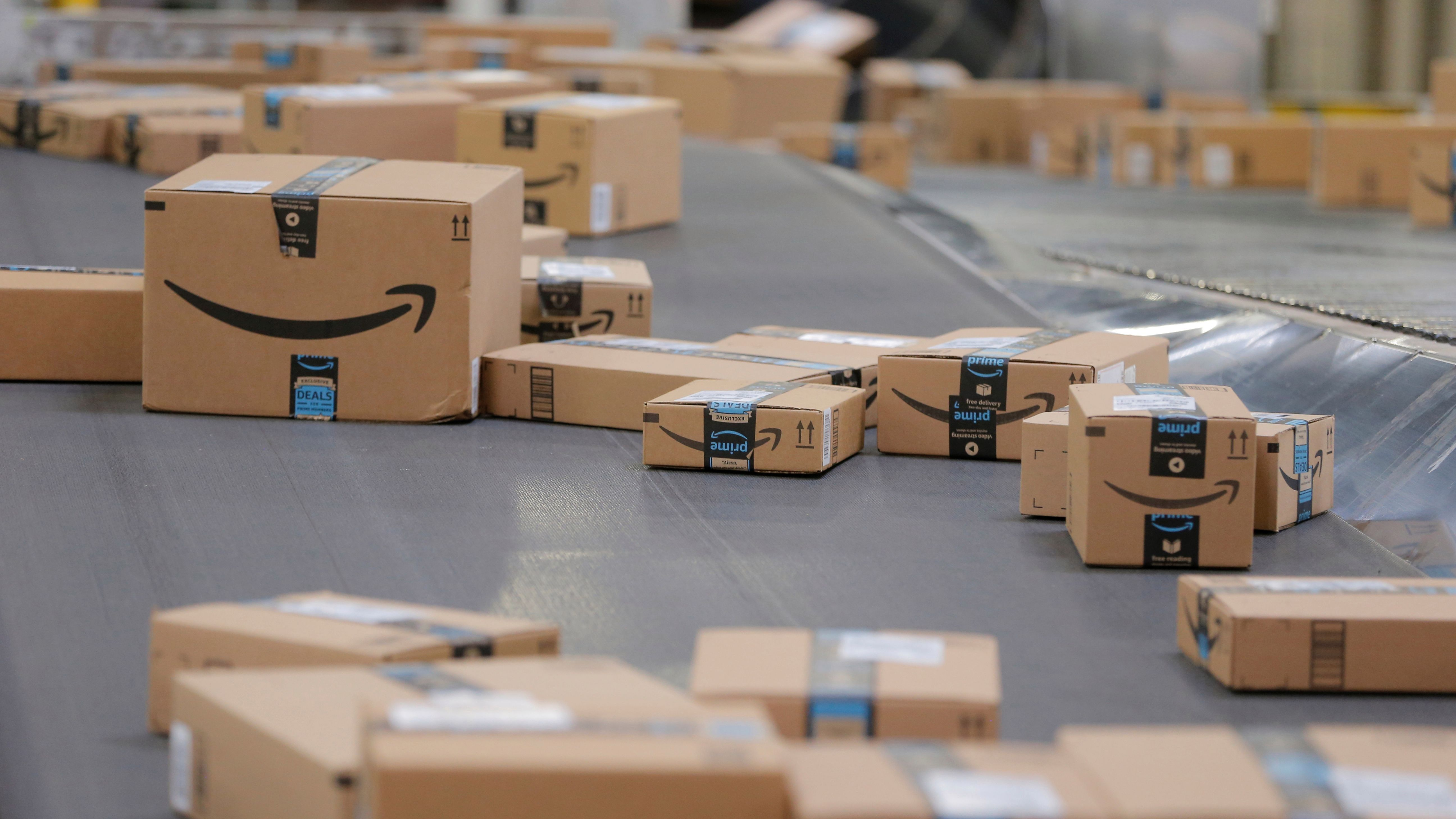 Amazon packages travel down a conveyor belt.